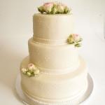 Cremefarbene Hochzeitstorte mit Rosen. Foto: Anett Noster White Rabbit