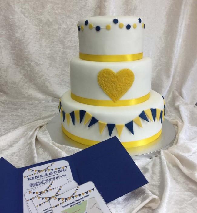Hochzeitstorte mit blau-gelben Fähnchen und Herz. Foto: White Rabbit Bremen