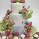 Dreistöckige Hochzeitstorte und Cupcakes mit Hortensien und Rosenblüten. Foto: White Rabbit Bremen