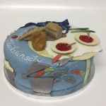 Torte mit Kochtopf und Fischen, Esstisch und Geschirr. Foto: White Rabbit Bremen